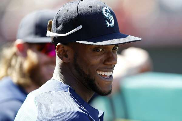 FILE - In this Sunday, Sept. 16, 2018 file photo, Seattle Mariners' Cameron Maybin smiles with a teammate in the dugout during the fourth inning of a baseball game in Anaheim, Calif. A person with direct knowledge of the negotiations says free agent outfielder Cameron Maybin is closing in on a minor league contract with the San Francisco Giants, who were still in the market for outfielders to add depth at the position. Maybin must pass a physical, the person said Saturday, Feb. 16, 2019, speaking on condition of anonymity because the deal wasn't complete. The agreement would have an invitation to major league camp at spring training. (AP Photo/Alex Gallardo, File)
