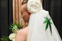 A cannabis artist who goes by the name Green Tiger Lilly poses for a photo while wearing a bouquet and wearing a veil at the Cannabis Wedding Expo at Westfield Mall in San Francisco on Sunday, Feb. 17, 2019.