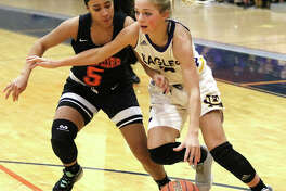 CM freshman Kelbie Zupan (right) drives on Springfield Lanphier's Tionna Traylor during Thursday's championship game at the Rochester Class 3A Regional. CM won and takes a 28-5 record to Monday's Taylorville Sectional.