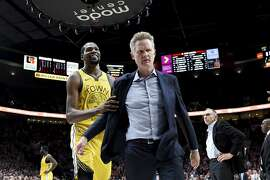 Golden State Warriors forward Kevin Durant, left, helps escort coach Steve Kerr after Kerr was ejected during the second half of the team's NBA basketball game against the Portland Trail Blazers in Portland, Ore., Wednesday, Feb. 13, 2019. The Blazers won 129-107. (AP Photo/Steve Dykes)