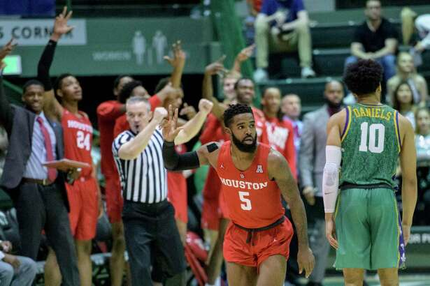 Houston guard Corey Davis Jr. (5) celebrates a three-pointer with teammates against Tulane guard Caleb Daniels (10) in the second half of an NCAA college basketball game in New Orleans, Sunday, Feb. 17, 2019. Houston won, 85-50. (AP Photo/Matthew Hinton)