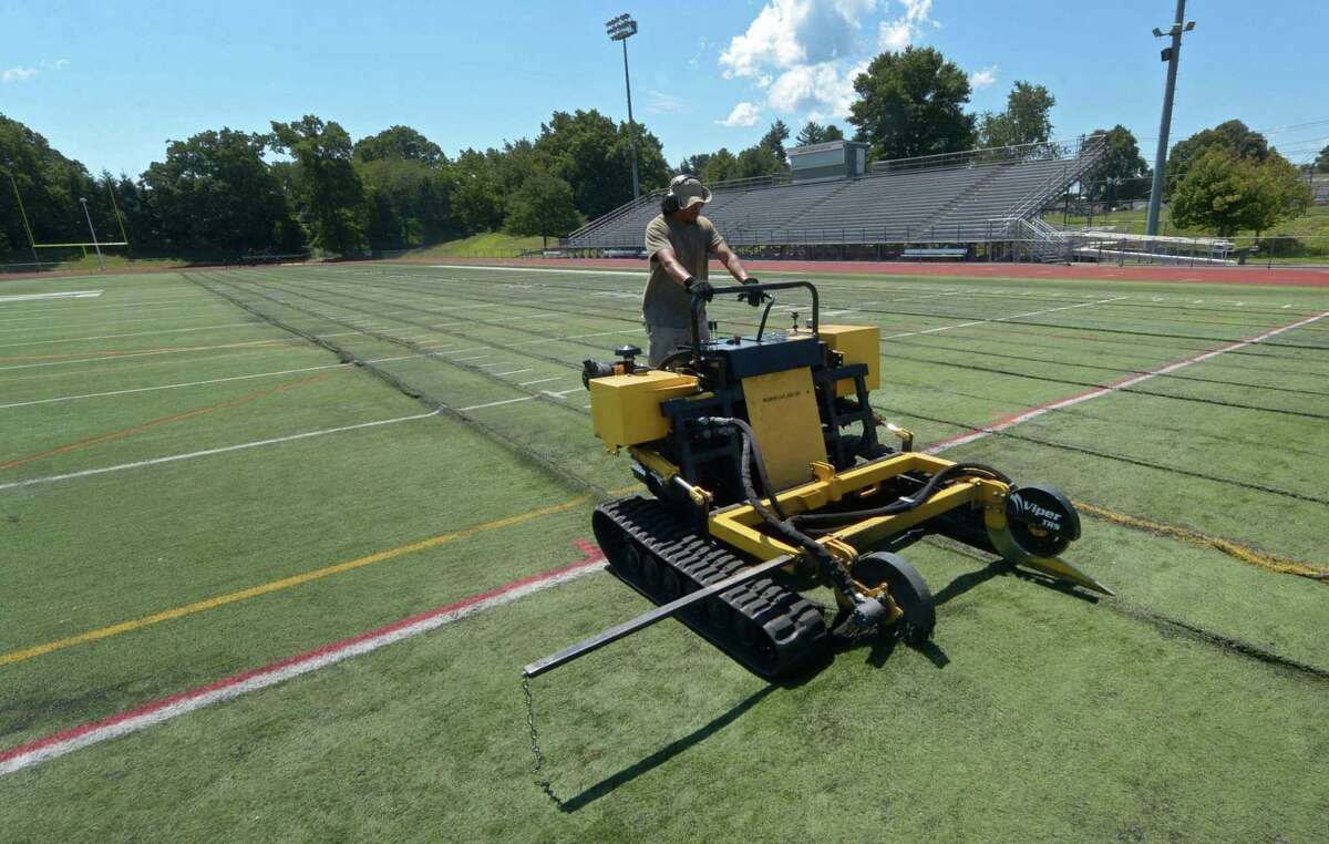 Workers with Field Turf remove the old artificial turf from Norwalk High School's Testa Field last July.
