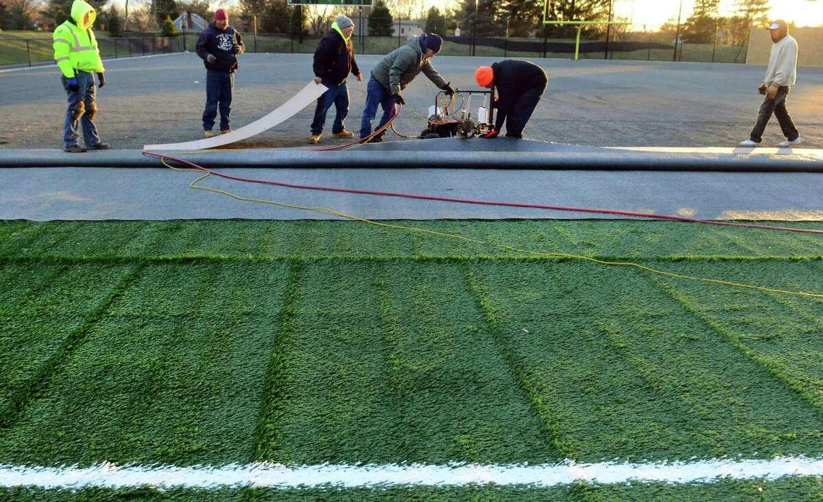 Crew members from Sprinturf install a new artificial turf field at Platt Tech High School in Milford in 2016.