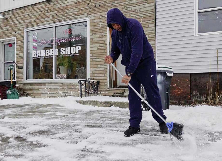 Paris Payne, manager of First Impressions Barber Shop on Clinton Ave., clears snow off the sidewalk outside the shop on Monday, Feb. 18, 2019, in Albany, N.Y.    (Paul Buckowski/Times Union) Photo: Paul Buckowski, Albany Times Union / (Paul Buckowski/Times Union)