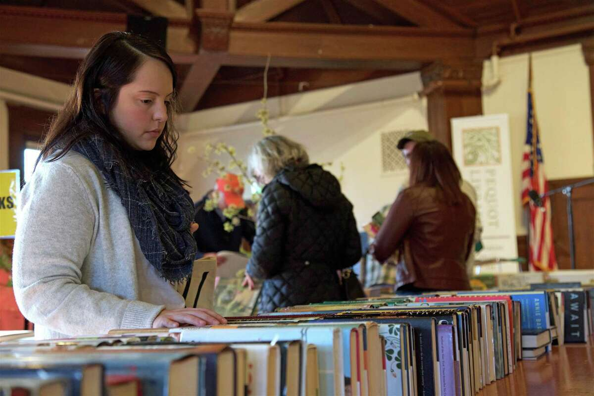 Sara Evans of Bridgeport explores the selection at the Pequot Library's annual Mid-Winter Book Sale on Saturday, Feb. 16, 2019, in Fairfield, Conn.