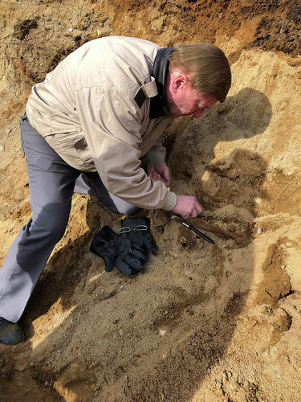 In this Feb. 11, 2019 photo provided by Michael S. Borgos, Esq., local archeologist David Starbuck searches for artifacts in a construction site in Lake George, N.Y., after skeletal remains were found of people believed to have died during the Revolutionary War. Skeletal remains of as many as 11 people believed to have died during the Revolutionary War have been uncovered at a construction site in upstate New York, a lawyer for the couple who owns the property told The Associated Press Tuesday, Feb. 12, 2019.