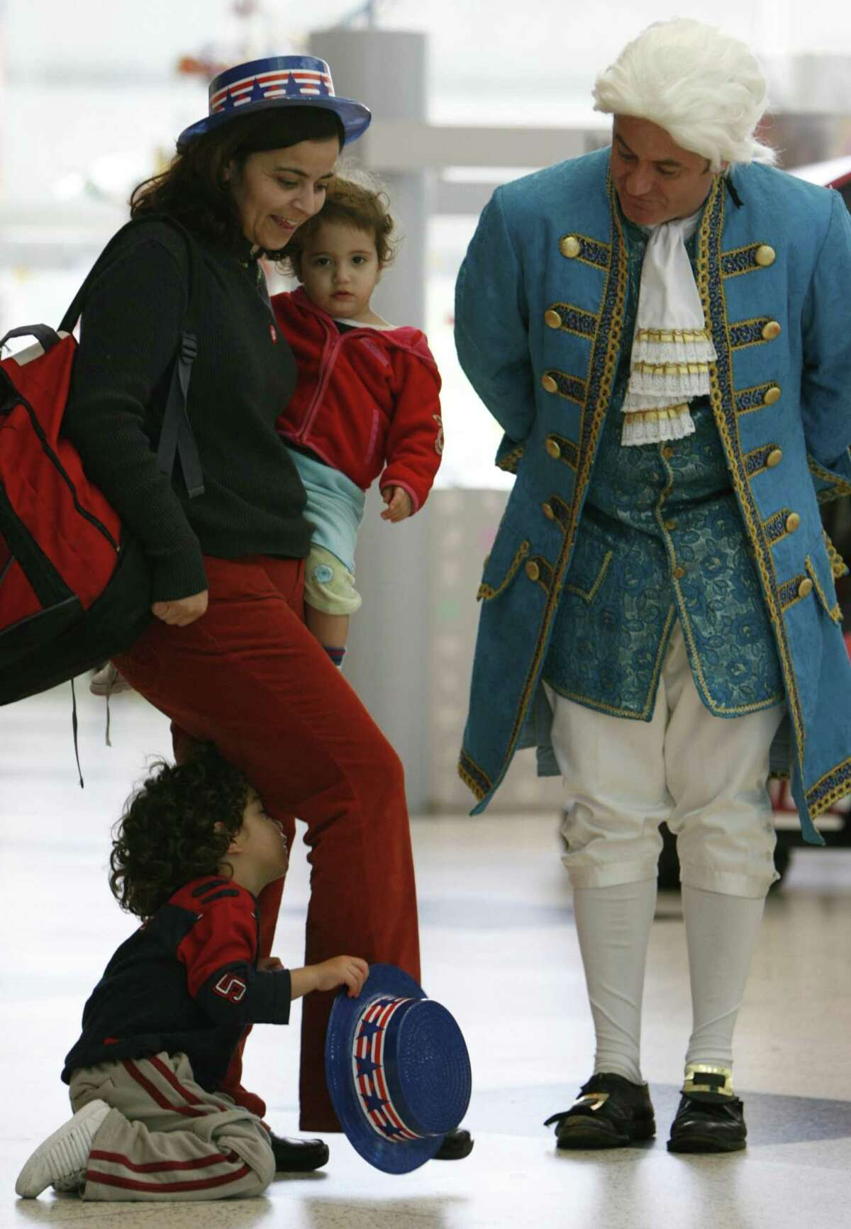 Efrat Hazan Ozeri, left, holds her daughter, Naama Ozeri, 2, as her son, Liam Ozeri, 3, hides from George Washington played by David Born during President's Day activities at The Children's Museum of Houston, Monday, Feb. 20, 2006. (AP Photo/Houston Chronicle, Melissa Phillip) ** MANDATORY CREDIT: NO SALES, MAGS OUT, TV OUT, INTERNET: **