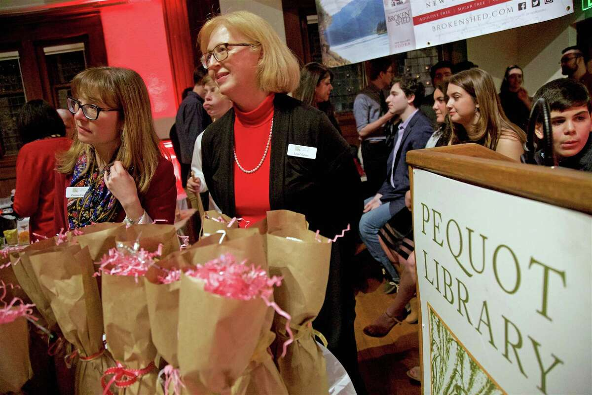 """Chief Librarian Christine Catallo, left, and Librarian Leslie Mahtini help out with fundraising at the Pequot Library's first-ever """"Head over Heels"""" Valentine's Day party on Thursday, Feb. 14, 2019, in Fairfield, Conn."""