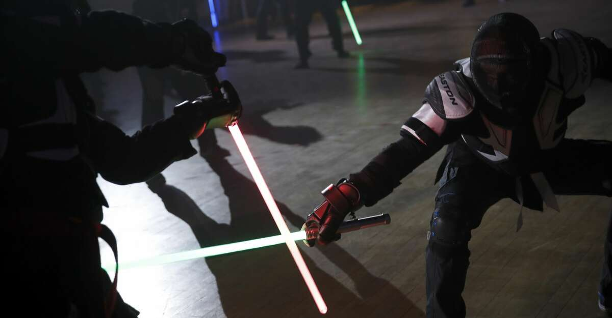 In this Sunday, Feb. 10, 2019, photo, competitor battles during the national lightsabers tournament in Beaumont-sur-Oise, north of Paris. In France, lightsaber fighting is an official sport, recognized as such by the French Fencing Federation. The sport's practitioners, many but not all of the fans of 'Stars Wars,' have had to build the discipline's competition rules almost from scratch. (AP Photo/Christophe Ena)