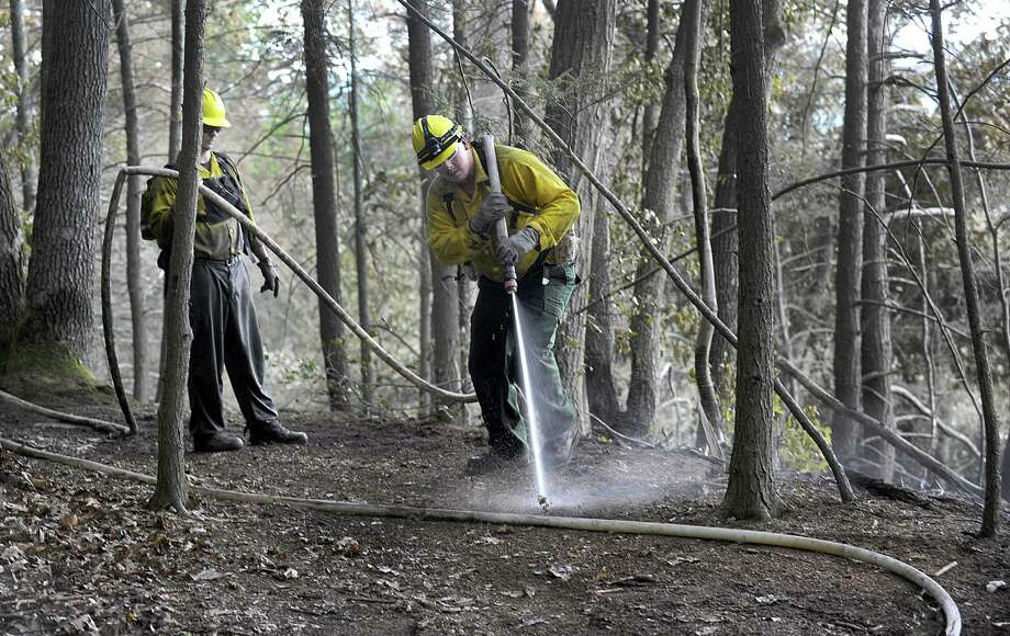 Rich Opalnenik, left, and Jeff Dery, with the Connecticut Department of Environmental Protection, are part of a crew still working Monday afternoon, July 25, 2016, to put out a fire at Lovers Leap State Park. The Park in New Milford reopened Monday after a massive brush fire that burned through the weekend was put out Sunday evening, according to the state's Department of Energy and Environmental Protection. Photo: Carol Kaliff / Carol Kaliff / The News-Times