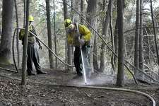Rich Opalnenik, left, and Jeff Dery, with the Connecticut Department of Environmental Protection, are part of a crew still working Monday afternoon, July 25, 2016, to put out a fire at Lovers Leap State Park. The Park in New Milford reopened Monday after a massive brush fire that burned through the weekend was put out Sunday evening, according to the state's Department of Energy and Environmental Protection.