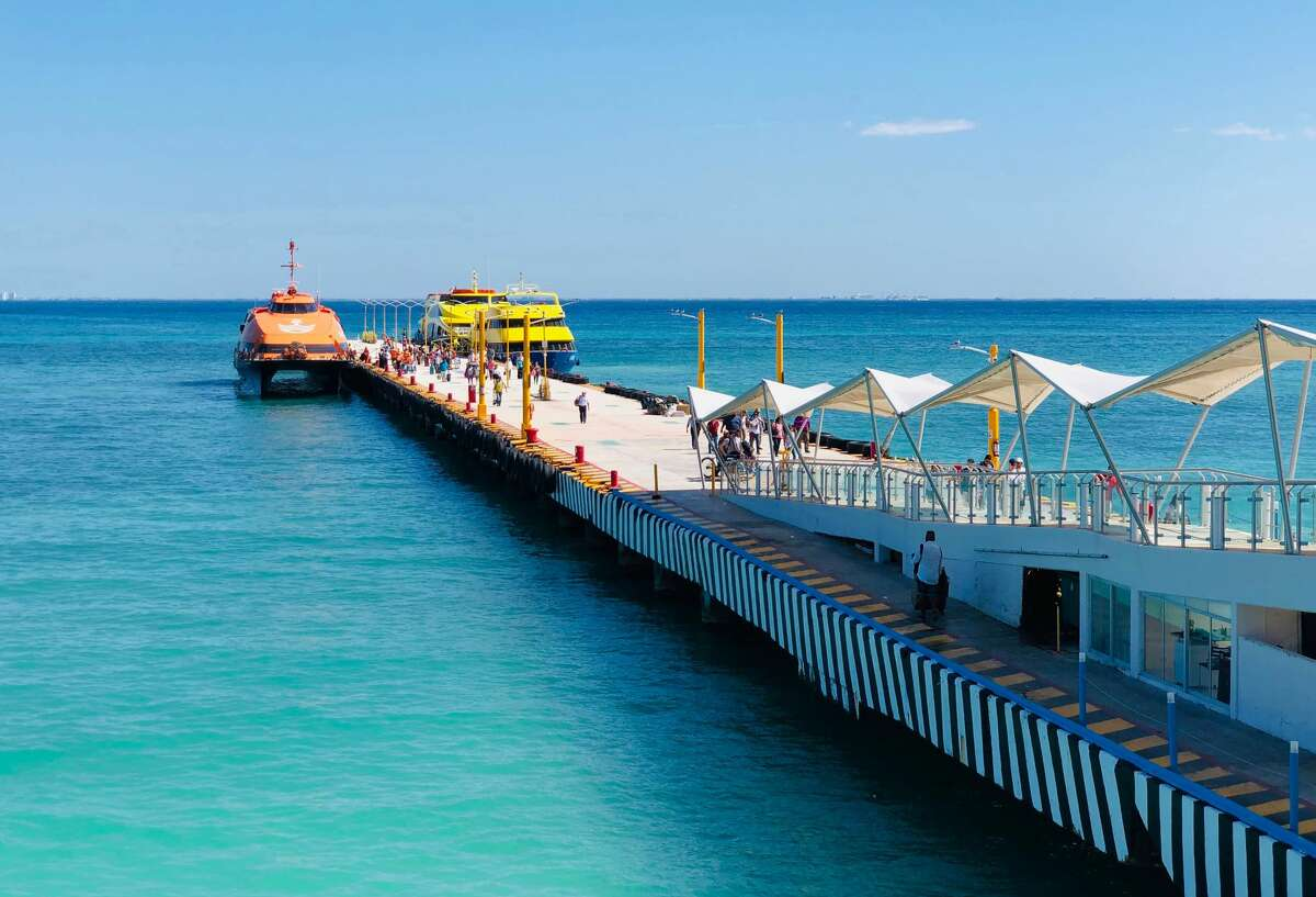 People walk on the pier of the ferries to the island of Cozumel, in the seaside tourist resort of Playa del Carmen, Quintana Roo State. (Photo by Daniel SLIM / AFP)
