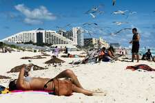 A flock of seagulls flies over beachgoers in the seaside tourist resort of Cancun, in Quintana Roo state, Mexico on February 16, 2019. - Playa del Carmen and Cancun are the top tourist destinations in Mexico, famous for their turquoise waters and white-sand Caribbean beaches. (Photo by Daniel SLIM / AFP) (Photo credit should read DANIEL SLIM/AFP/Getty Images)