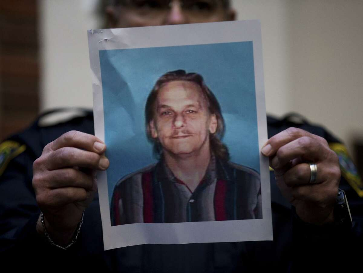 A Houston Police officer holds up the photo of one of the suspects , 59-year-old Dennis Tuttle, during a news conference at Memorial Hermann Hospital on Tuesday, Jan. 29, 2019 in Houston. An attempt to serve a search warrant at a suspected drug house on Monday, quickly turned into a gunbattle that killed two suspects and injured five undercover narcotics officers, including four who were shot, Chief Art Acevedo said. The other suspect, Rhogena Nicholas was shot and killed as she tried to grab the service weapon of the first officer to be injured, Acevedo said. (Godofredo A. Vasquez/Houston Chronicle via AP)