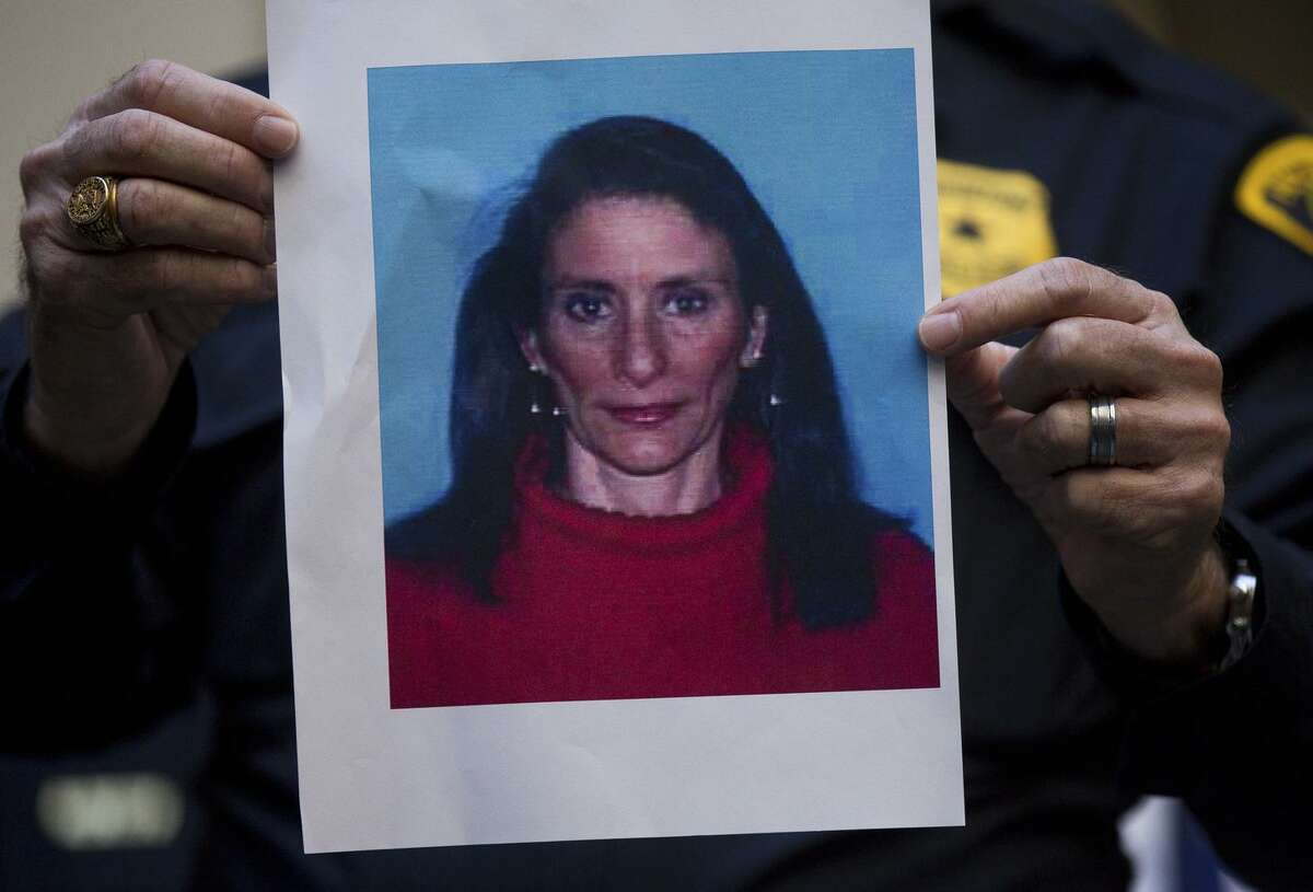 A Houston Police officer holds up the photo of one of the suspects, Rhogena Nicholas, during a news conference at Memorial Hermann Hospital on Tuesday, Jan. 29, 2019 in Houston. An attempt to serve a search warrant at a suspected drug house on Monday, quickly turned into a gunbattle that killed two suspects and injured five undercover narcotics officers, including four who were shot, Chief Art Acevedo said. Nicholas, was shot and killed as she tried to grab the service weapon of the first officer to be injured, Acevedo said. The second suspect killed was 59-year-old Dennis Tuttle. (Godofredo A. Vasquez/Houston Chronicle via AP)