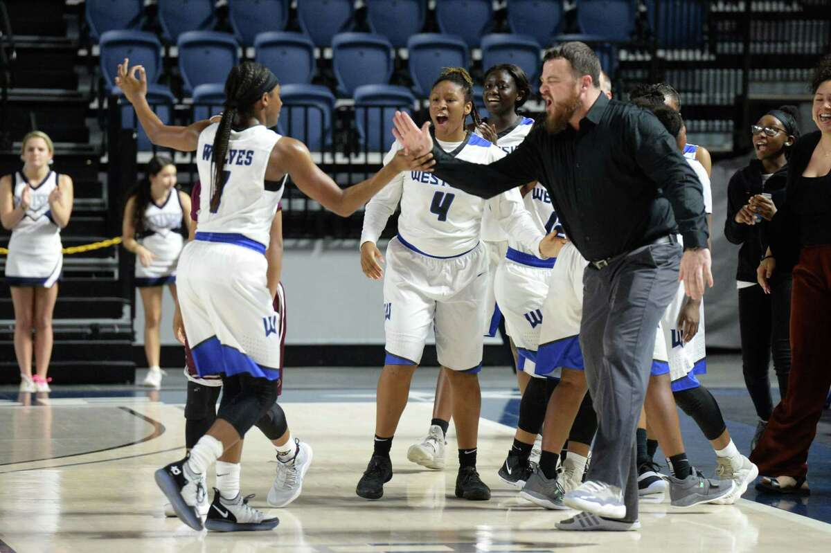 The Wolves react to their lead at the end of the first quarter of a Class 6A, Region III area-round basketball playoff game between the Westside Wolves and the Kempner Cougars on Friday at Delmar Fieldhouse, Houston, TX.
