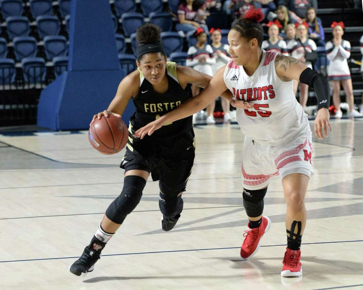Alicia Blanton (15) of Foster drives past Jordan Walker (25) of Goose Creek Memorial during the second half of a Class 5A, Region III area-round basketball playoff game between the Foster Falcons and the Goose Creek Memorial Patriots on Friday, February 15, 2019 at Delmar Fieldhouse, Houston, TX.