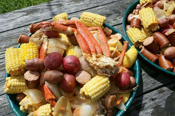 The finished low-country boil containing shrimp, snow crab legs, sweet corn, mesquite smoked sausage, quartered onions and red potatoes seasoned with Old Bay seasoning, garlic cloves, bay leaves, quartered lemons and kosher salt.