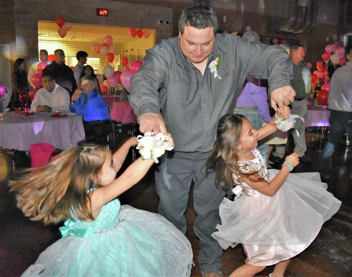 Thomas Smith twirls kindergartner Hannah Griffin, left, and second-grader Jessica Griffin as they all dance to a lively tune played by the DJ during the February Daddy-Daughter Dance at Needville High School.