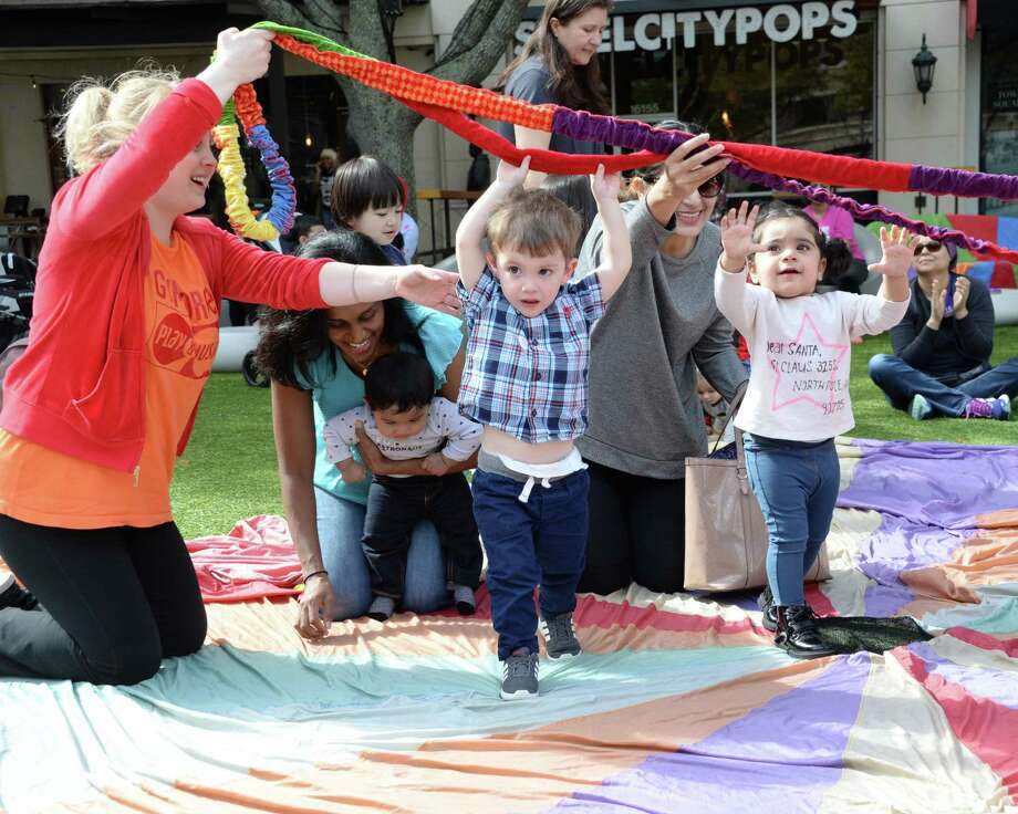 Parents and children enjoy a Parachute Play Time organized by the Missouri City location of Gymboree Play & Music at Sugar Land Town Square on Thursday. Photo: Craig Moseley, Houston Chronicle / Staff Photographer / ©2019 Houston Chronicle