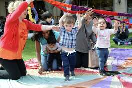 Parents and children enjoy a Parachute Play Time organized by the Missouri City location of Gymboree Play & Music at Sugar Land Town Square on Thursday.
