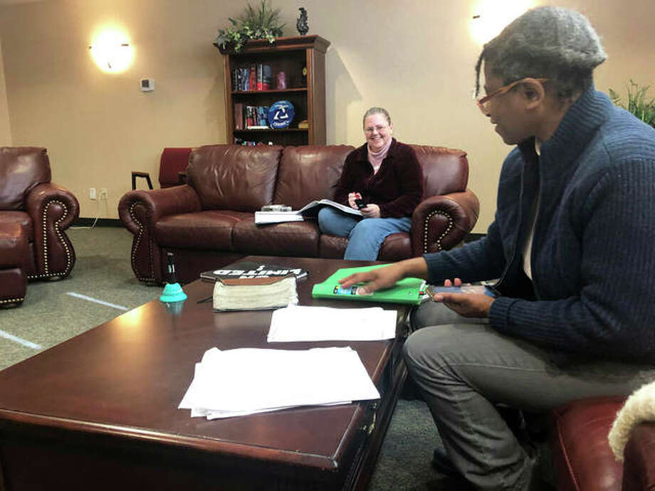 AJ French, Gift of Voice president and CEO, background, and Michelle Tibbs, board director, talk in between calls Friday. The group would ring the blue bell, pictured on the table, to celebrate a donor's contribution. Photo: Brittany Johnson | The Intelligencer