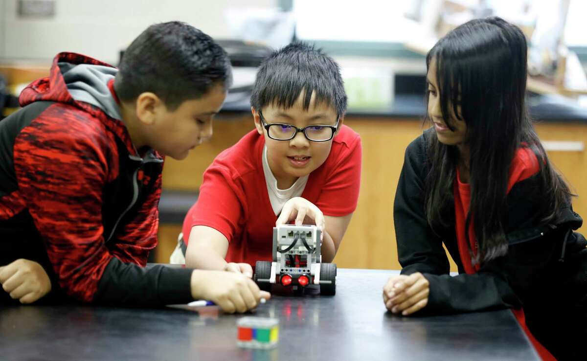 At an engineering class in HISD's Stevenson Middle School, Daniel Martinez, Victor Le and Kimberly Turrubiartes build a Lego robot.