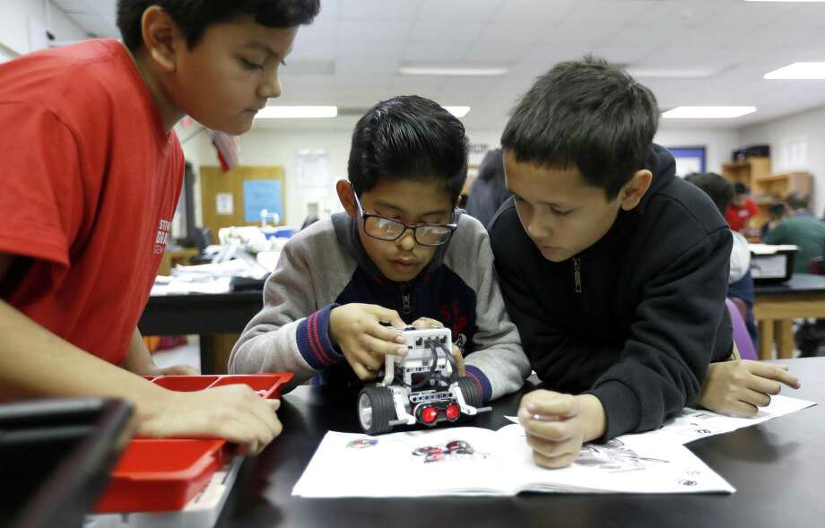 Alessandro Hidalgo, center, works with his teammates Lemuel Pacheco, left, and Alexander Molina as they built a Lego robot in engineering teacher Jason Bradley's class at Stevenson Middle School in HISD where immigrant students are focusing on STEM, Monday, Jan. 28, 2019, in Houston. Photo: Karen Warren, Houston Chronicle / Staff Photographer / © 2019 Houston Chronicle