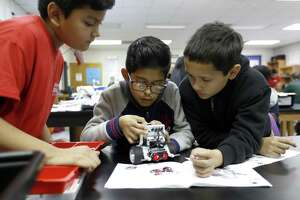 Alessandro Hidalgo, center, works with his teammates Lemuel Pacheco, left, and Alexander Molina as they built a Lego robot in engineering teacher, Jason Bradley's class at Stevenson Middle School in HISD where there are students focusing on STEM who are immigrants, Monday, Jan. 28, 2019, in Houston.