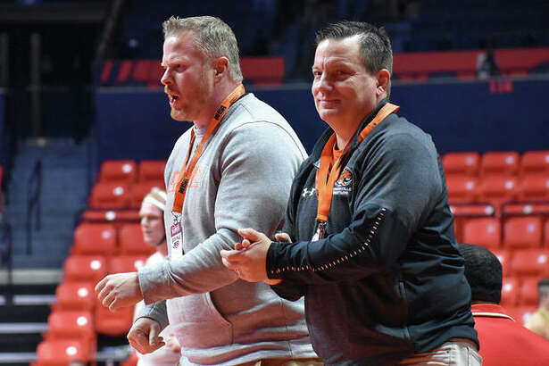 Edwardsville head coach Jon Wagner, right, and assistant coach Doug Heinz celebrate after Lloyd Reynolds picks up a victory in a consolation match Friday.