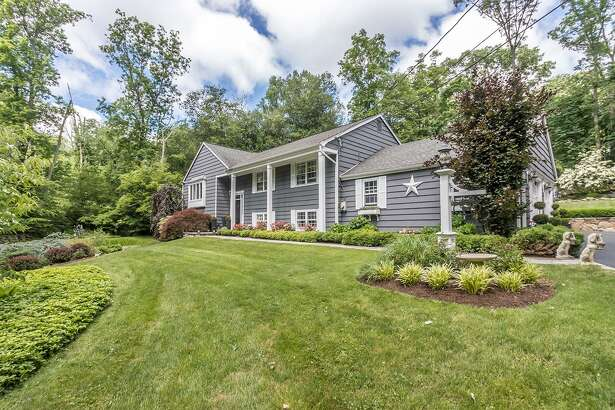 The southern colonial-inspired raised ranch sits atop a knoll on a 2.2-acre level and gently sloping property at 28 Ironside Road in Greenfield Hill.