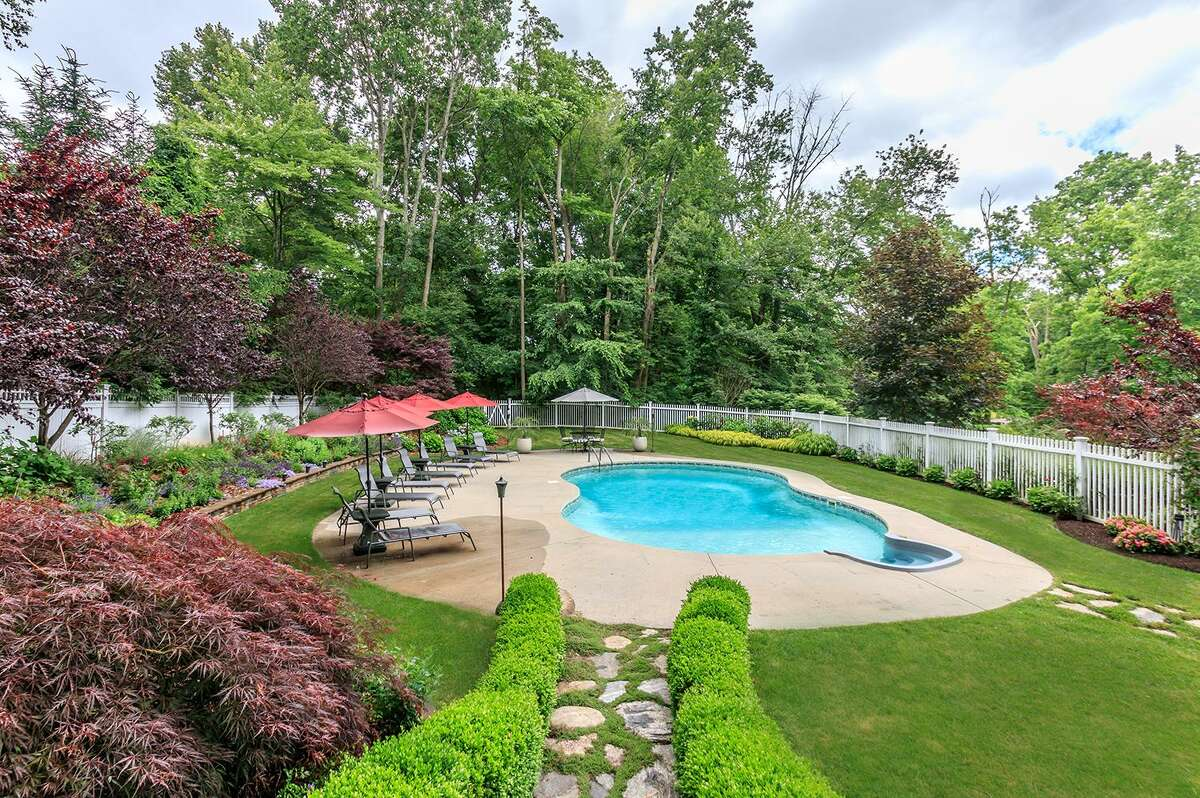 The backyard features a private area with a heated in-ground swimming pool and pool house that the current owners call Club Ironside.