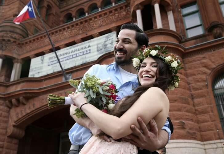 Nathan Ramirez, 25, hugs his bride-to-be, Caitlyn Hughes, 26, in front of the Bexar County Courthouse, Thursday, Feb. 14, 2019. The couple have known each other since high school and decided on ValentineÕs Day to get married, Òbecause itÕs a day to celebrate love,Ó said Hughes. The two plan on moving to South Korea and start on their teaching careers. Thirty-six couples exchanged wedding vows in the 10 a.m. ceremony and another 62 couples were at the midnight service. Bexar County Clerk Lucy Adame-Clarke officiated the ceremonies with County Court at Law No. 13 Judge Rosie Gonzalez provided Spanish translation. Ceremonies were scheduled for Noon and 2 p.m.