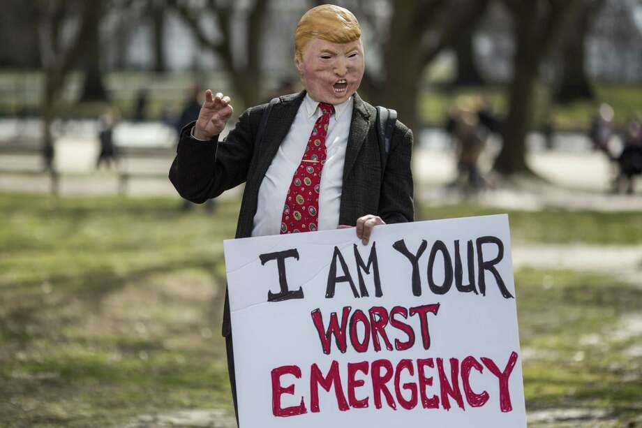 A demonstrator wearing a mask depicting President Donald Trump stands in Lafayette Square during a demonstration organized by the American Civil Liberties Union (ACLU) protesting President Donald Trump's declaration of emergency powers on Feb. 18 in Washington, DC. Photo: Zach Gibson / Getty Images / 2019 Getty Images