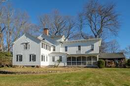 The house sits on a level property of just over four acres and features open porches, a screened porch, and a covered stone patio.