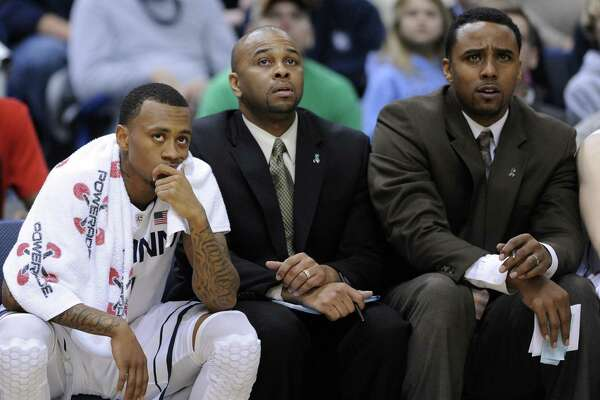 Ricky Moore, center, with Ryan Boatright (left) and Kevin Freeman (right)during a UConn loss to Villanova on Feb. 16, 2013. Moore will not be in Hartford when UConn's 1999 national title team is honored Sunday.