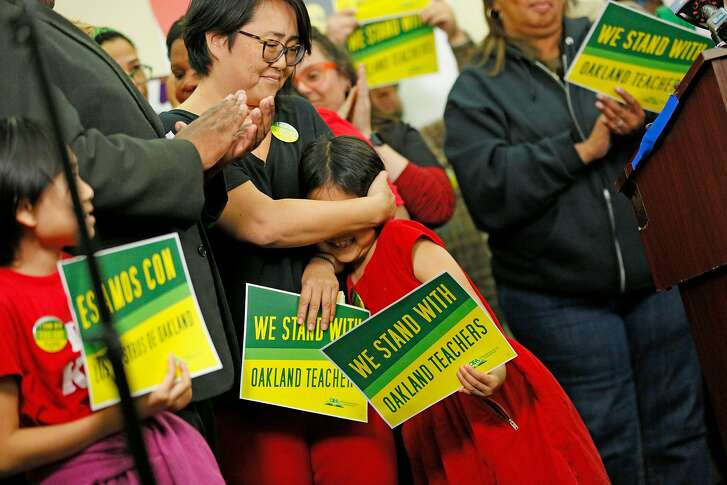 Liz Suk embraces her daughter Sena Yoo, an Oakland second grader, during a news conference at the Oakland Education Association office on Saturday, Feb. 16, 2019, in Oakland, Calif. The OEA announced teachers will strike on Thursday in a call for higher wages and more investment in city schools.