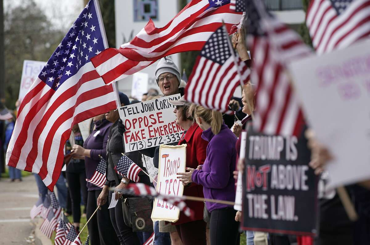 Alex McDonald of Houston, center, stands among protesters rallying along Memorial Drive outside the Houston office of Senator John Cornyn Monday, Feb. 18, 2019, in Houston. The event was part of nationwide protests against the national emergency declaration by President Donald Trump. (Melissa Phillip/Houston Chronicle via AP)
