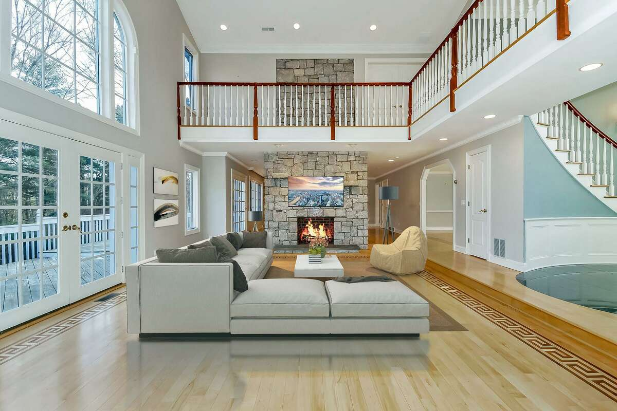 In the great or family room there is a floor-to-ceiling quarried stone fireplace, an interior balcony, and French doors to a sizable raised wood deck. A border design is inlaid in the living room floor.
