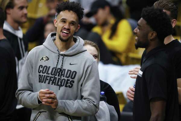 San Antonio spurs guard Derrick White, left, jokes with his former Colorado teammate Namon Wright before the second half of an NCAA college basketball game between Arizona State and Colorado on Wednesday, Feb. 13, 2019, in Boulder, Colo. Colorado won 77-73. (AP Photo/David Zalubowski)