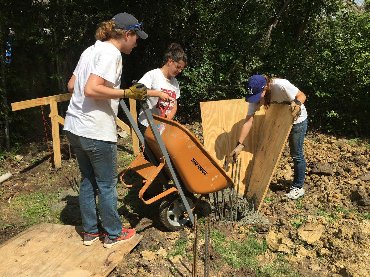 From left, Rice students Rose Wilkowski, Leyla Hepsaydir, Julie Klosterman pour concrete footings at the site where the unit was installed.
