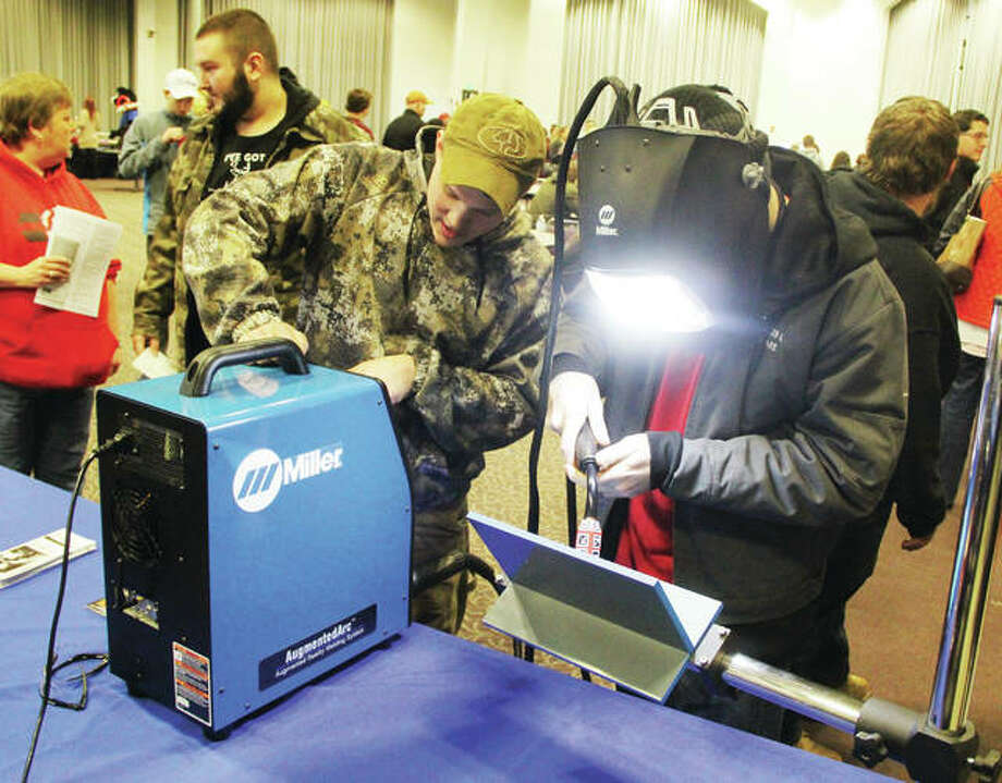 Alton High School senior Caleb Link, right, uses a virtual reality welding simulator while Lewis and Clark Community College welding student Andrew Cresswell watches during Discover Day at the college Monday. About 300 parents and students came out to look over LCCCs programs and services during the event, held twice each year at the campus. Photo: Scott Cousins | The Telegraph