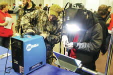 Alton High School senior Caleb Link, right, uses a virtual reality welding simulator while Lewis and Clark Community College welding student Andrew Cresswell watches during Discover Day at the college Monday. About 300 parents and students came out to look over LCCCs programs and services during the event, held twice each year at the campus.