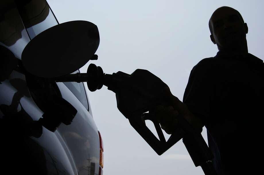 In this June 27, 2008 file photo, a person pulls a gas pump from his vehicle after filling his tank in Philadelphia. The nation's psyche is battered and bruised, the sense of pessimism palpable. The Independence Day holiday is typically a time to honor all that we are as a nation, but the feeling is there's less to celebrate on this our 232nd birthday. Happy? It would seem not. (AP Photo/Matt Rourke, file) Photo: Matt Rourke / AP 2008