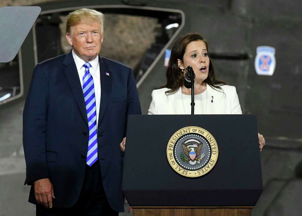 President Donald Trump, left, listens as Rep. Elise Stefanik, R-N.Y., speaks before signing a $716 billion defense policy bill named for John McCain Monday, Aug. 13, 2018, in Fort Drum, N.Y.