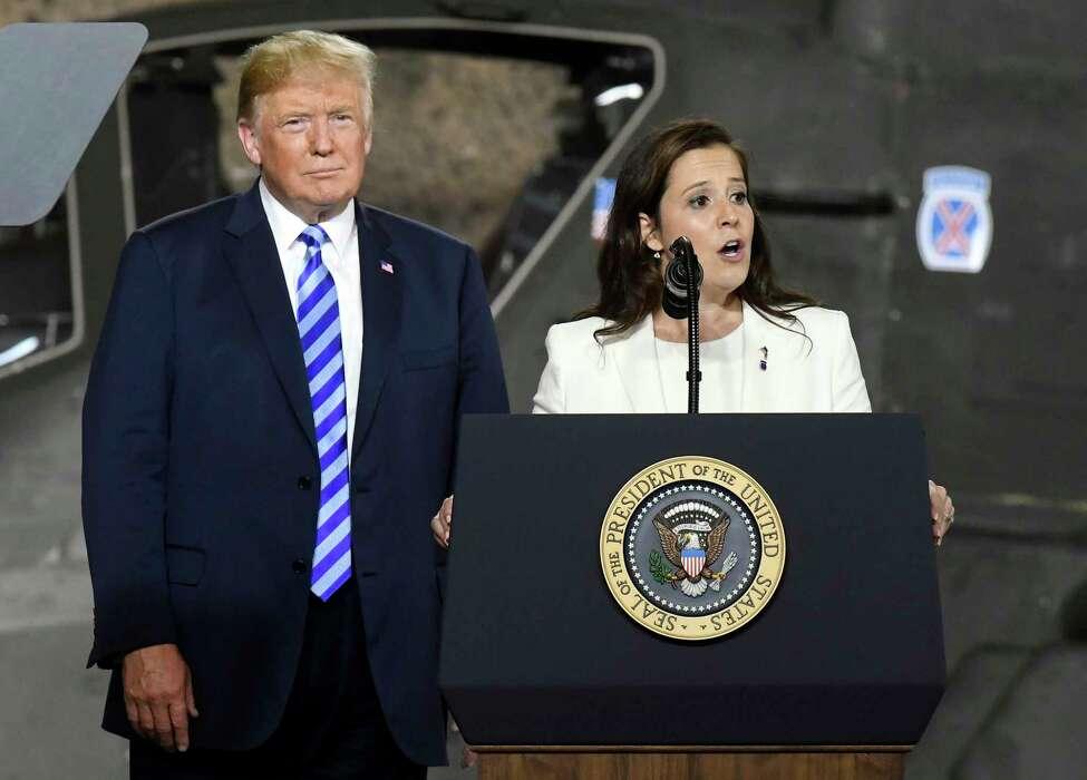 President Donald Trump, left, listens as Rep. Elise Stefanik, R-N.Y., speaks before signing a $716 billion defense policy bill named for John McCain Monday, Aug. 13, 2018, in Fort Drum, N.Y.