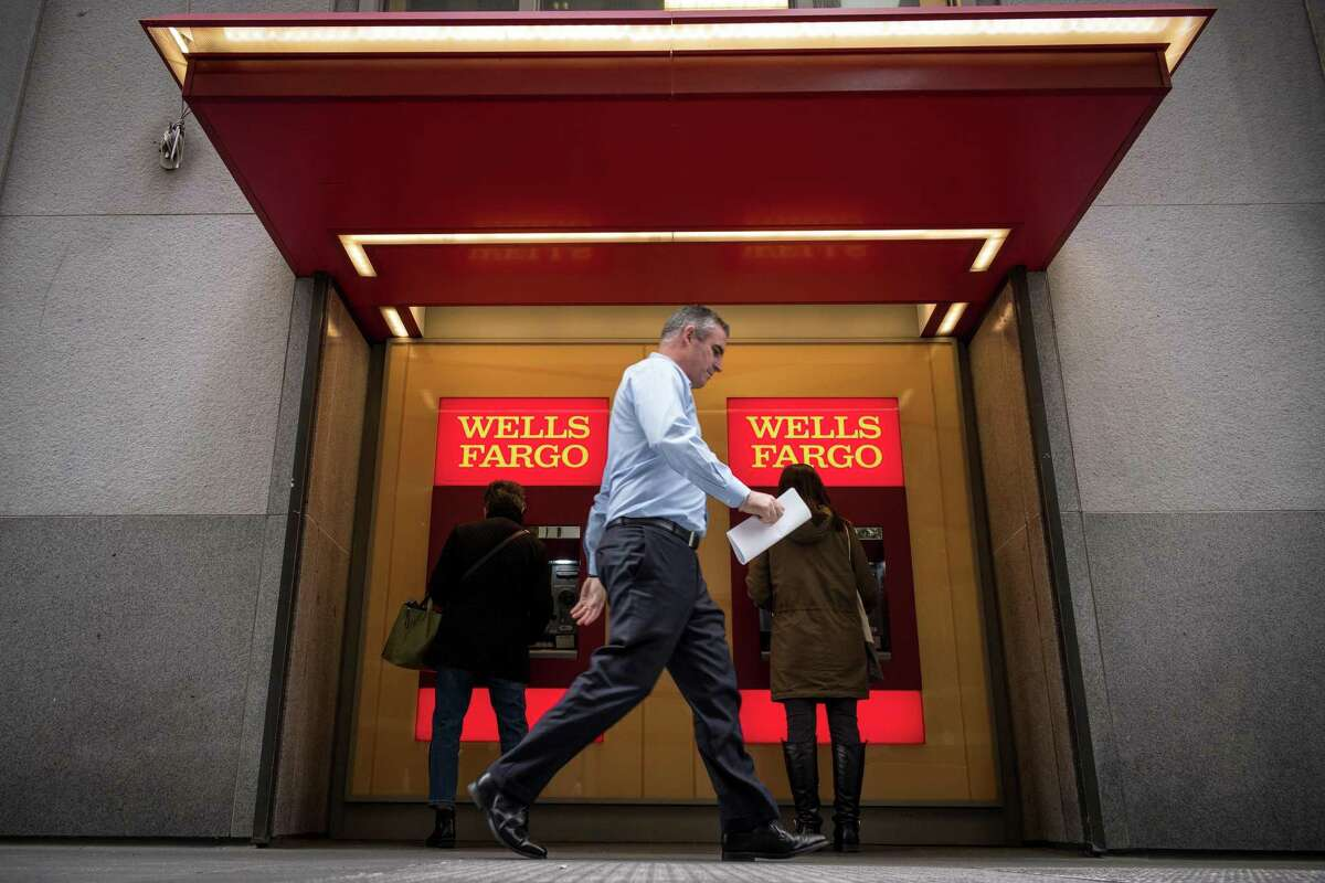 Customers use an ATM machine in front of a Wells Fargo Bank branch in San Francisco, Calif. on Friday, Feb. 8, 2019.