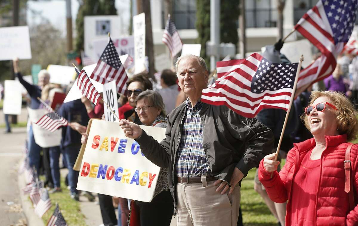 Protesters rally along Memorial Drive outside the Houston office of Senator John Cornyn Monday, Feb. 18, 2019, in Houston. The event was part of nationwide protests against the national emergency declaration by President Donald Trump.