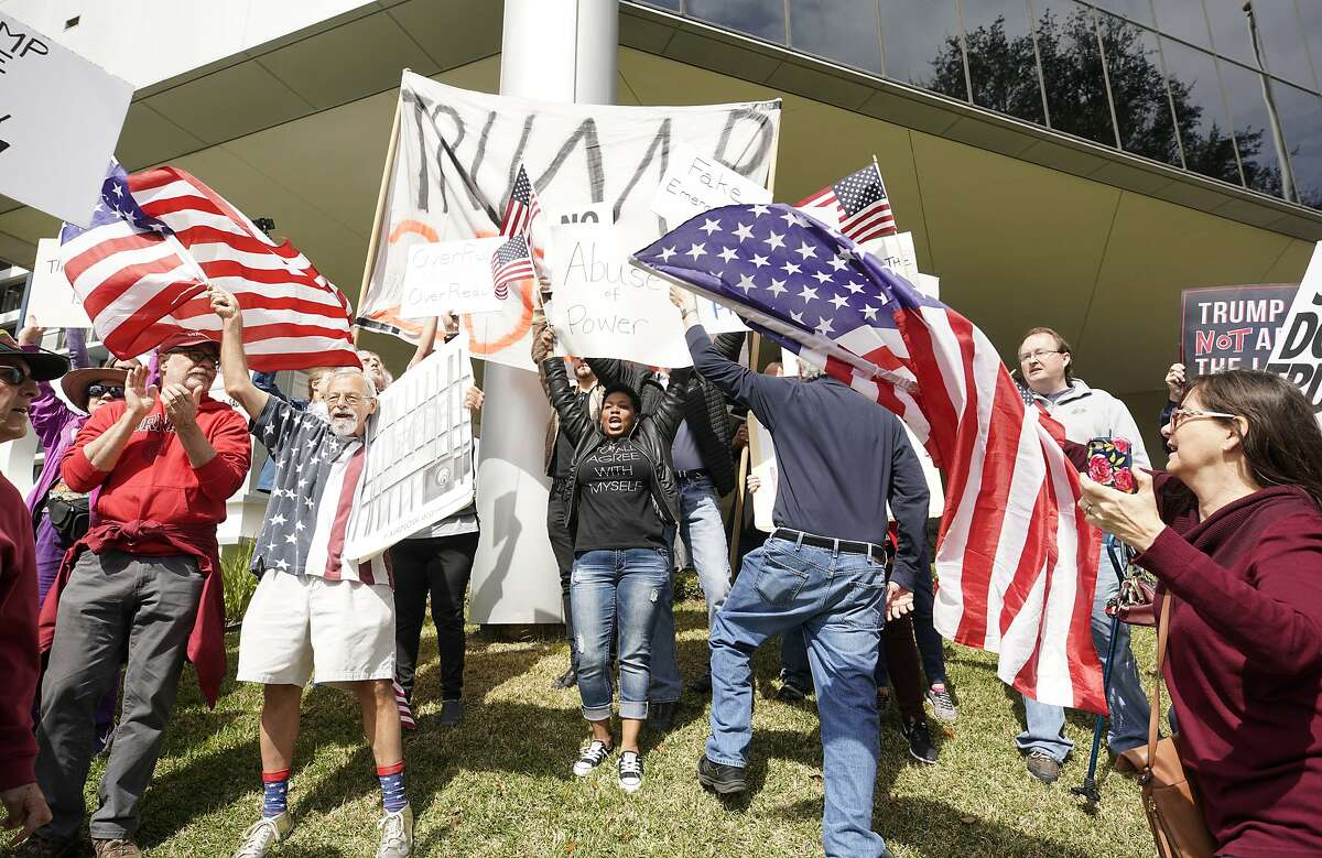 Anti-Trump protesters move to cover a large sign held by Trump supporters who tried to mix into the crowd during a rally along Memorial Drive outside the Houston office of Senator John Cornyn Monday, Feb. 18, 2019, in Houston. Police quickly intervened to move the Trump supporters away from the crowd. The event was part of nationwide protests against the national emergency declaration by President Donald Trump.