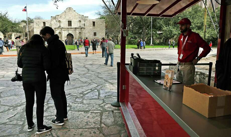 """Tourists look through a brochure they picked up at the new Alamo """"Welcome Center,"""" Feb. 18. A reader wants the city to recognize those who may be buried beneath Alamo grounds. Photo: Bob Owen /San Antonio Express-News / ©2019 San Antonio Express-News"""